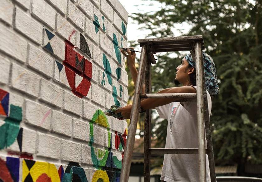 Artist Keith Pinto working on a mural